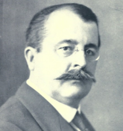 Head and shoulders of a man with receding hair, rimless glasses and a heavy moustache. Formally dressed with collar and tie, he is facing right but his eyes are turned to the camera.