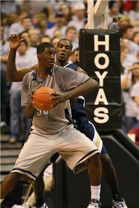A African-American teenage basketball player wearing a gray uniform looks over his shoulder at another playing in a blue uniform. Behind them are fans and a basketball hoop with the word