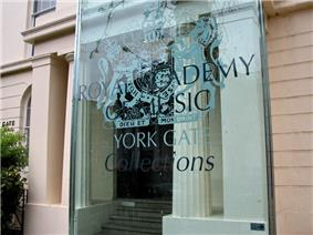 a classical building with a modern sign identifying it as the Royal Academy of Music