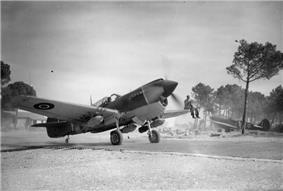 Single-engined fighter plane on airfield with propeller spinning and man sitting on left wing