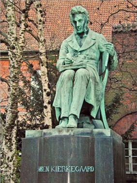 A statue. The figure is depicted as sitting and writing, with a book on his lap open. Trees and red tiled roof is in background. The statue itself is mostly green, with streaks of grey showing wear and tear. The statue's base is grey and reads
