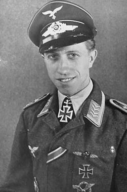The head and upper body of a young man, shown in semi-profile. He wears a peaked cap and military uniform with various military decorations, at his neck, an Iron Cross displayed at the front of his white shirt collar.