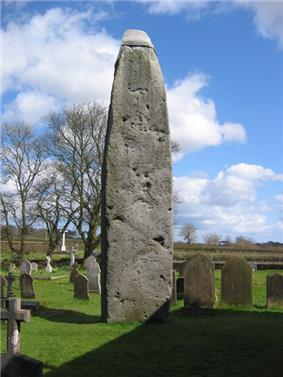 a cemetery over which towers a large standing stone with some sort of cap
