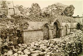 Sepia image showing remains of synagogue entrance arches blocked up with stones.