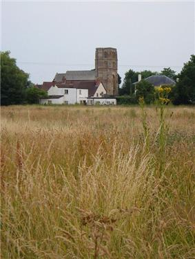 Stone building with square tower showing across fields.