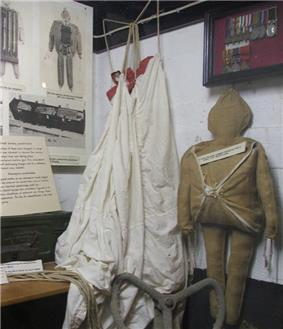 canvas figure with white parachute displayed in front of right diagrams and a medal case
