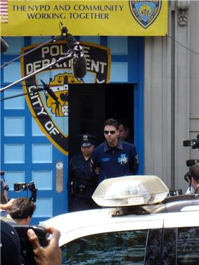 Two police officers escorting a man wearing sunglasses and a blue shirt out of a door in a wall on a city street. The wall and door are painted with the logo of the New York City Police Department. Above it is a promotional banner with the words