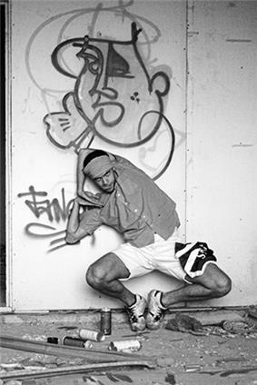 A black and white photo of a Russian popper posing mid-dance in front of a graffiti painted wall on the side of an industrial building.