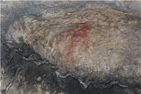 A red figure painted on the rock