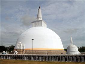 A large white stupa with an orange border near the bottom.
