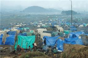 View of refugee camp on foggy day, showing tents of various colours and the refugees