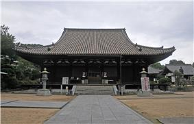 Wooden building with a hip-and-gable roof.