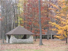Rustic picnic shelters, one stone and one timber, with red, orange and yellow leaves on surrounding trees