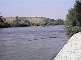A broad river runs between rocky banks