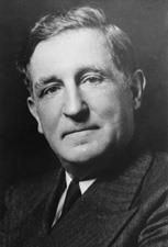 A middle-aged man wearing a coat and tie looks into the camera.