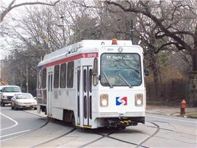 A white single-car trolley in street running.