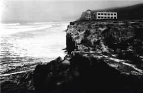 Historic photograph of the Old Scripps Building, a rectangular structure on a clifftop overlooking the Pacific breakers.