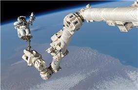 A photograph of a long, white mechanical arm stretching out above a mostly blue planet displaying white clouds and brown terrain all under a black expanse