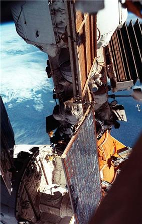 A view showing a module covered in white insulation with a smaller module, covered in orange insulation, connected to the end of it. Part of a space shuttle can be seen attached to the orange module, and a number of folded and unfolded solar arrays are visible. The limb of the Earth forms the backdrop.