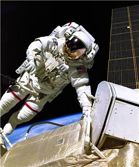 An astronaut in a white spacesuit with a red, white, and blue flag on the left shoulder in the foreground with a black background