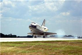 A spaceplane, coloured white on its topside and black on its underside, lands on a runway. A strip of turf is visible in the foreground, there are trees in the background and there is a cloud of smoke coming from the spaceplane's rear wheels.