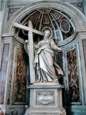 A marble statue showing a matronly woman in a sweeping cloak supporting a cross which stands beside her and presenting a set of nails to the viewer with her left hand