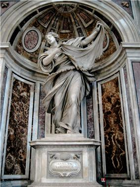 This statue shows the saint as a young woman, who, with a sweeping dramatic gesture, displays a cloth on which there is an image of the face of Jesus.