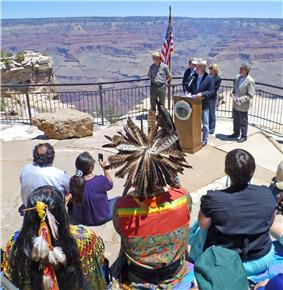 American flag and group of four or five speakers at a podium in front of audience including a Native American in headdress
