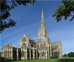 A long shot of Salibury Cathedral shows the building rising from a green lawn, with its tall grey masonry spire against the blue sky. The exterior shows the same harmony in the groupings of simple windows that is apparent in the interior view.