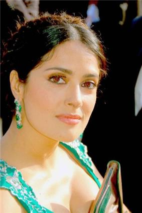Head and shoulders shot of Hayek looking right, wearing emerald earrings with matching dress
