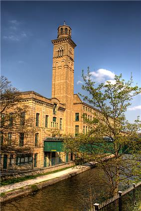 A three story pale red brick building along the left side of a small river. The building has a bell tower rising out of the middle of it.
