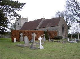 Gray stone building with red tiled roof, partially obscured by a hedge. A square tower is at the far end. The foreground includes several crosses and gravestones.