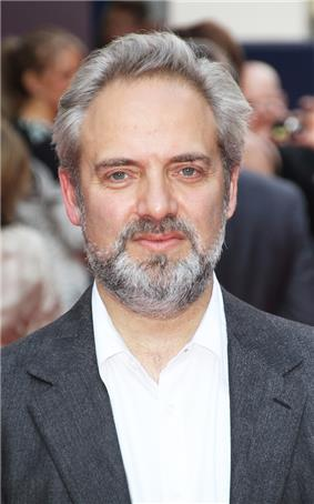 Profile of a grey haired, bearded man smiling. He wears an unbuttoned white shirt accompanied with a grey suit.