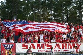American fans, dressed in red, cheer in bleachers as they hold a large American flag over themselves at a soccer match.
