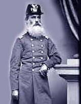 An 1870 black and white photograph of a white male army cavalry officer with a long full white beard age 60 in full military uniform wearing an older style dragoon headwear.