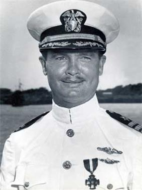 Head and shoulders of a white man with a thin mustache wearing a white peaked cap, its black visor decorated with oak leaves, and a white military jacket with dark shoulder boards and one medal and two winged pins on the left breast.
