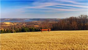 A red bench on a large expanse of brown cut grass, overlooking rolling forested hills and a lake