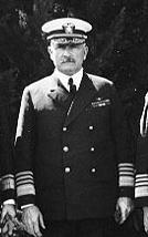 A black-and-white image of a tall man with a mustache in a naval uniform