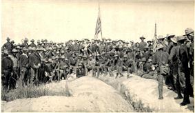 A black and white photo of US Army soldiers on 3 July 3, 1898, in an upside down V type formation on top of Kettle Hill; two American flags are center and right. Soldiers facing camera.