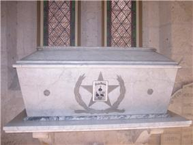 A white marble coffin sits on a ledge in front of stained glass windows. On the front of the coffin is a large 5-pointed star. Engraved within the star are the words