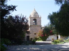 Photograph of the bell tower of Carmel Mission, with a peaked dome atop with gardens in the foreground.