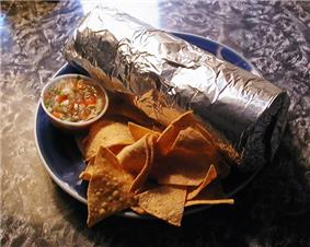 A Mission-style burrito, wrapped in aluminum foil, with tortilla chips and salsa