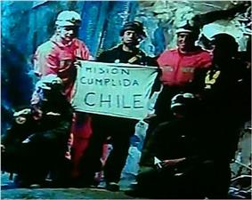Slightly grainy color video capture image of the six rescuers displaying the famous