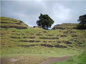A series of semi-collapsed dry-stone terraces, overgrown with short grass. On top of the uppermost of five terraces stand the crumbling, overgrown remains of two large buildings flanking the ruins of a smaller structure. A tree grows from the right hand side of the smaller central building, and another stands in at extreme right, on the upper terrace and in front of the building also standing on it. The foreground is a flat plaza area, with the collapsed flank of a grass-covered pyramid at bottom right. The sky is overcast with low rainclouds.