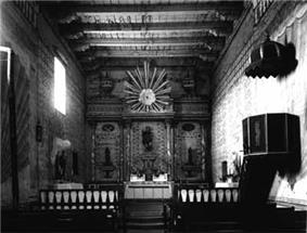 Historic interior photograph of the sanctuary at Mission San Miguel Arcángel. Beamed wooden ceilings and adobe walls protect an ornate altar, chancel, and pulpit.