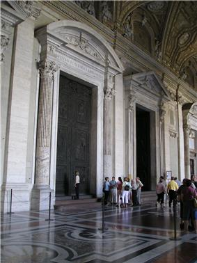 Photo shows view of vestibule with three huge doorways leading to the church's interior. The doors are framed by columns and have pediments. The floor is of inlaid marble. The nearest doorway is closed by two huge ancient bronze doors. A group listens to a tour guide while one woman examines the doors.