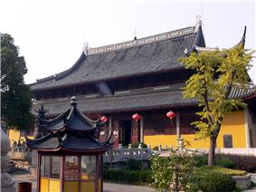 A tall, two-story building painted bright yellow. Each story has a separate roof. The corners of top roof curves sharply upward, while the bottom roof barely curves at all.