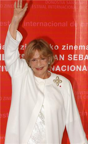 Jeanne Moreau in front of a red background, waving