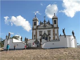 Stairs leading to a white stone church with two towers. Sculptures are placed on walls in front of the church.