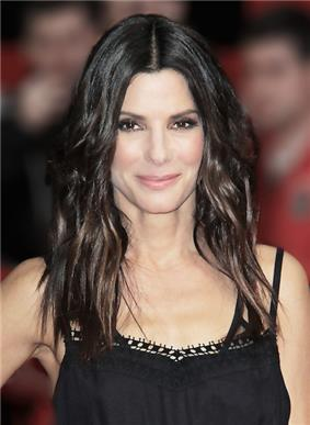 A picture of a brown hair lady wearing her hair down. She wears a black dress.